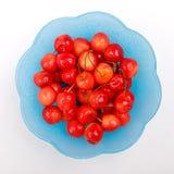 Взгляд сверху к зрелым ягодам вишни с капельками воды в голубую плиту на белой предпосылке Стоковое Фото