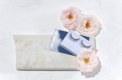 Взгляд сверху ложных ресниц отражение зеркала и неба в нем, мягких розах на части камня на белой предпосылке стоковые изображения