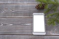Взгляд сверху мобильного телефона лежа на настольном компьютере, расклад экрана изолированная белизна Стоковые Фото