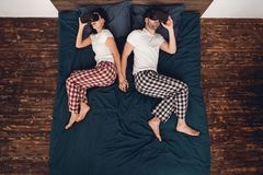 Взгляд сверху Молодая женщина и человек лежат на кровати и смотрят в стеклах виртуальной реальности Домашний отдых стоковые фотографии rf