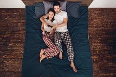 Взгляд сверху Молодая пара в пижамах играет gamepads в видеоигре, лежа на кровати в доме Стоковое Изображение RF