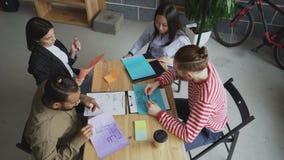Взгляд сверху молодой азиатской женщины деля архитектурноакустические планы с мульти-этнической командой и обсуждая новый start-u видеоматериал