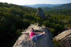 Взгляд сверху молодой женщины делая йогу работает лежать na górze большого утеса горы на яркий летний день стоковая фотография