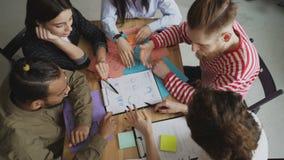 Взгляд сверху молодой команды мужских и женских коллег дела наблюдая и обсуждая новые start-up диаграммы проекта внутри сток-видео