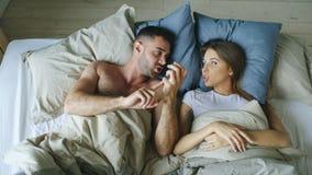 Взгляд сверху молодых пар лежа в кровати осадило и спорит один другого стоковое изображение rf