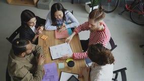 Взгляд сверху мульти-этнической команды кладет ладонь совместно счастливо и продолжает обсудить новый проект в современном офисе  акции видеоматериалы