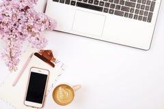 Взгляд сверху настольного компьютера женского работника с компьтер-книжкой, цветками и различными деталями канцелярские товаров Ж Стоковая Фотография RF
