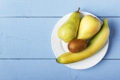 Взгляд сверху на деревянной ristic таблице с плодоовощ кучи зрелым на белой плите Плодоовощ груш, банана и кивиа для здоровых зав Стоковые Изображения RF