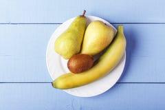 Взгляд сверху на деревянном столе с свежими фруктами кучи Плодоовощ груш, банана и кивиа на белой плите скопируйте космос Стоковое Изображение