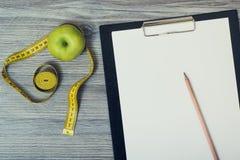 Взгляд сверху на настольном компьютере с зеленым яблоком и рулеткой, доской сзажимом для бумаги стоковые изображения