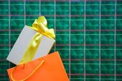 Взгляд сверху на подарочной коробке с желтой лентой смычка и хозяйственной сумке апельсина на яркой ой-зелен оранжевой шотландско стоковая фотография rf