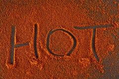 Взгляд сверху на предпосылке текстуры порошка перца красных чилей при текст изолированный на темной предпосылке Стоковое Изображение