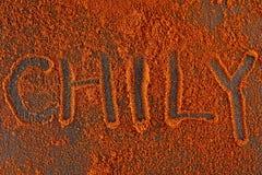Взгляд сверху на предпосылке текстуры порошка перца красных чилей с текстом на темной предпосылке Стоковое Фото
