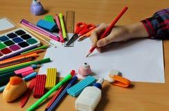 Взгляд сверху на таблице с чистым листом бумаги и руки младенца с карандашем задняя школа к Краски цвета с кистями, карандашами стоковые изображения rf