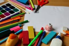 Взгляд сверху на таблице с чистым листом бумаги Назад к концепции школы с космосом для текста Краски цвета с кистями, карандашами стоковое фото