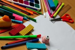 Взгляд сверху на таблице с чистым листом бумаги Назад к концепции школы с космосом для текста Краски цвета с кистями, карандашами стоковое фото rf