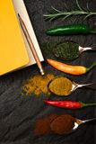 Взгляд сверху на тетради состава для рецепта и восточных специях в ложках и перцах на черном металлическом подносе в азиатском ст стоковое фото rf