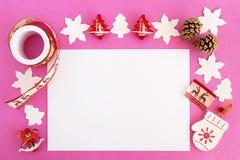 Взгляд сверху на украшениях рождества, конусах сосны и белом листе бумаги на розовой предпосылке Стоковые Фотографии RF