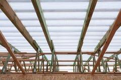 Взгляд сверху низкого угла новой деревянной крыши с надежными разделами и поддерживая лучами под белой windproof мембраной стоковые изображения rf