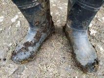 Взгляд сверху ног в черных темных грязных резиновых ботинках или wellingtons в грязи и глине и поземе стоковое фото rf
