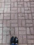 Взгляд сверху ног обувает ноги девушек, женщин в ботинках патента на предпосылке каменного конкретного квадрата вымощая прямоугол стоковая фотография rf