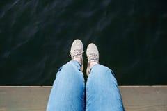 Взгляд сверху ног человека сидя на пристани над спокойным открытым морем стоковые изображения