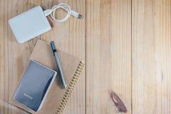 Взгляд сверху объекта перемещения: пасспорт и серый карандаш на коричневой тетради и жестком диске белизны внешнем на деревянном  Стоковая Фотография