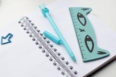 Взгляд сверху открытой пустой тетради с голубой в форме кролик ручкой, правителем и зажимами смешными kawaii стоковое изображение