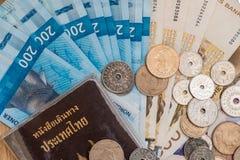 Взгляд сверху пасспорта Таиланда с валютой чеканит с наличными деньгами n Стоковые Фотографии RF