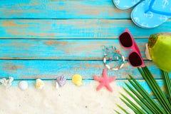 взгляд сверху песка пляжа при тапочка, кокос, солнечные очки, листья кокоса, морские звёзды, раковины, коралл и браслет сделанные Стоковые Изображения