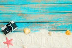 взгляд сверху песка пляжа с ретро камерой, морскими звёздами и раковинами на голубой деревянной предпосылке Стоковые Фотографии RF