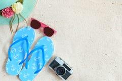 Взгляд сверху песка пляжа с соломенной шляпой, солнечными очками, тапочками и камерой Стоковая Фотография RF
