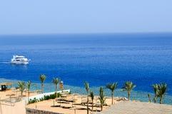 Взгляд сверху песчаного пляжа с sunbeds и зонтиками солнца и 2 большими белыми кораблями, шлюпкой, вкладышем круиза плавая в море стоковое фото