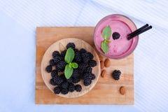Взгляд сверху питья ягоды с свежей мятой на голубой предпосылке ткани Деревянная плита с ежевиками на столе вырезывания Стоковые Фото