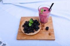 Взгляд сверху питья ягоды с свежей мятой на голубой предпосылке ткани Деревянная плита с ежевиками на столе вырезывания Стоковое фото RF