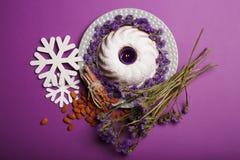 Взгляд сверху плиты с тортом кольца, свечой, миндалиной, циннамоном, снежинками, хворостинами цветков на фиолетовой предпосылке Стоковое Изображение