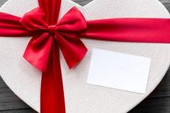 Взгляд сверху подарка настоящего момента праздника с красной лентой и опорожняет белую карточку стоковые изображения rf