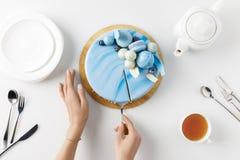 взгляд сверху подрезанных рук отрезая торт на прерывая доске Стоковые Фотографии RF