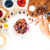 Взгляд сверху показывая руки есть кашу с гайками меда, голубиками на запачканном фокусе белого деревянного стола селективном, стоковые изображения