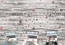 Взгляд сверху предпринимателей сидя на таблице и используя устройства Стоковые Изображения