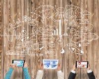 Взгляд сверху предпринимателей сидя на таблице и используя устройства Стоковая Фотография RF