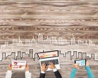 Взгляд сверху предпринимателей сидя на таблице и используя устройства Стоковое Изображение