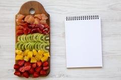 Взгляд сверху, прерванные свежие фрукты аранжировало на разделочной доске и тетради на белой деревянной предпосылке стоковое изображение
