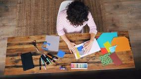 Взгляд сверху профессионального дизайнера работая на таблице делая бумажный коллаж вставляя диаграммы в тетради и режа формы акции видеоматериалы