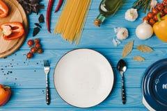 взгляд сверху пустых плиты и ингридиентов на голубой таблице Стоковая Фотография