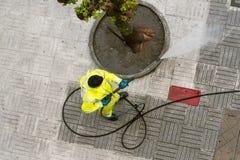 Взгляд сверху работника очищая тротуар улицы с высокой струей воды давления на дождливый день стоковые изображения