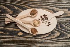 Взгляд сверху различных красочных трав и специй в ложке на деревенской коричневой деревянной предпосылке в концепции специи для з Стоковые Изображения