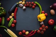 Взгляд сверху различных свежих зрелых овощей с доской шифера Стоковые Фото
