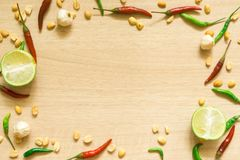 Взгляд сверху различных свежих овощей паприки, арахиса, чеснока, лимона и трав изолированных на деревянной предпосылке стоковые изображения rf