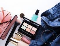 Взгляд сверху рубашки джинсов женщины, паллета concealer, лоска губы, маникюра, браслета, щетки порошка на белой предпосылке Стоковые Фотографии RF